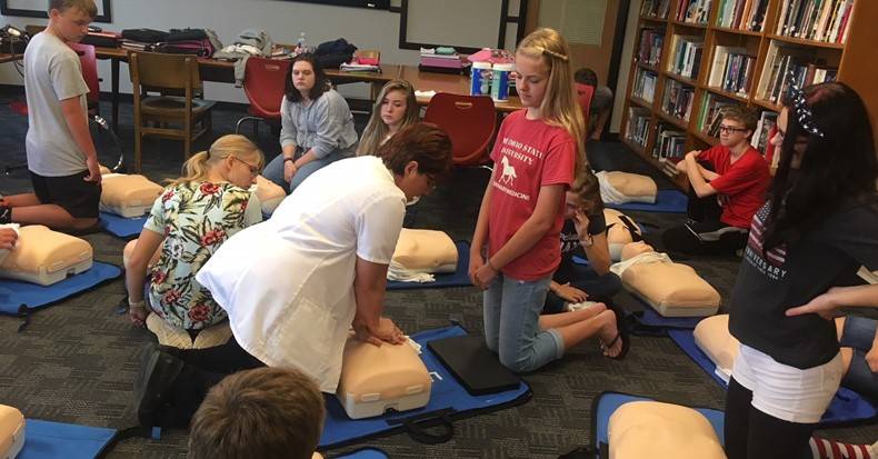 Students in Mrs. DeBos' health class learn CPR from district nurse Debbie Crank